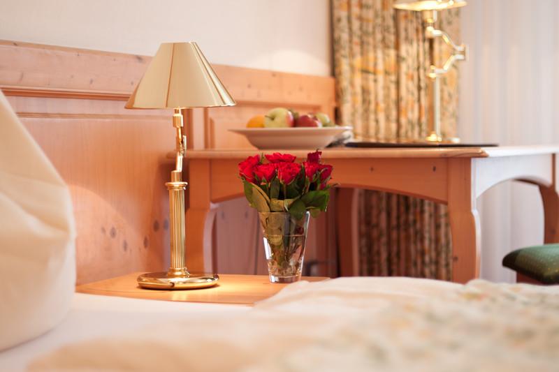 Bett mit Nachttisch und Tisch im Hintergrund