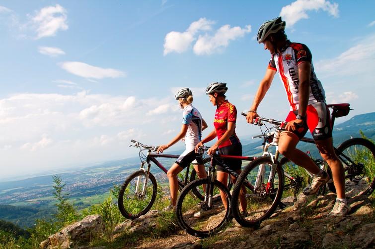 Drei Mountainbiker am Trauf mit Ausblick