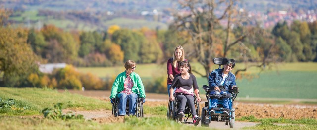 Drei Rollstuhlfahrer mit Begleitperson mit Burg Hohenzollern im Hintergrund