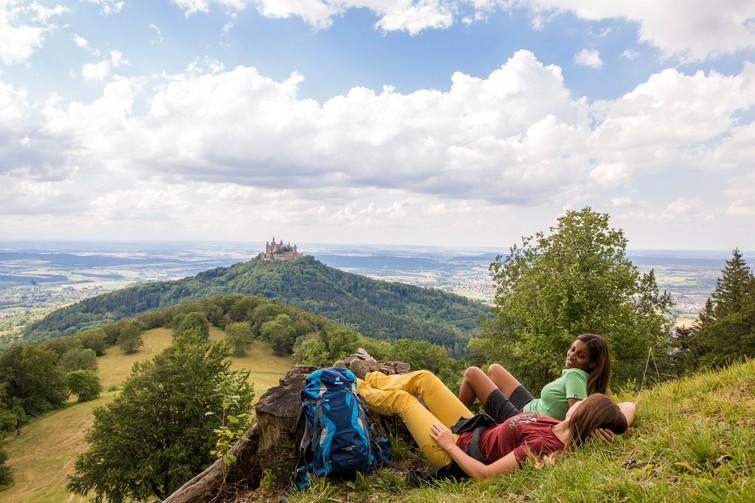 Wanderinnen liegen am Zeller Horn im Gras im Hintergrund Burg Hohenzollern