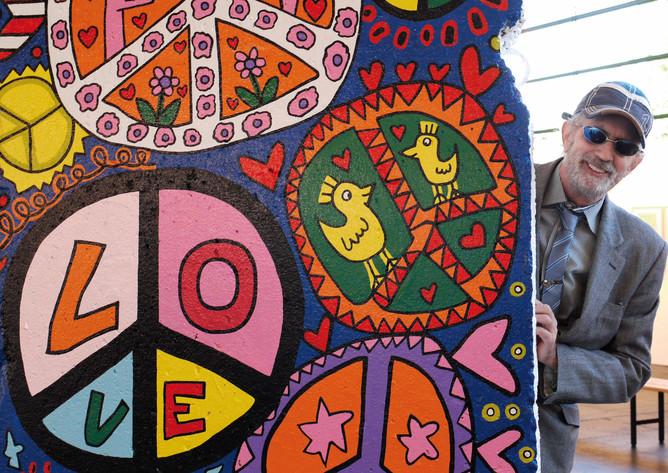 """2010, James Rizzi mit dem von ihm gestalteten Stück Berliner Mauer (""""In the Spirit of Peace"""")"""